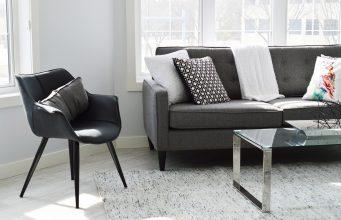Wnętrze domu; szare meble, biały dywan i przezroczysty stolik