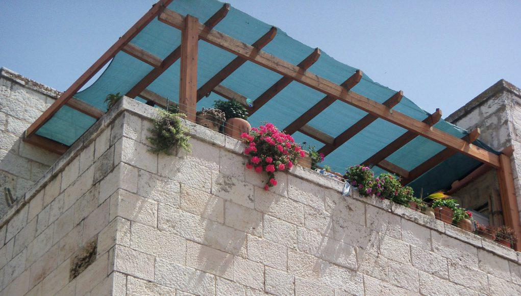 Balkon domu, nad nim wiata, na barierkach są donice z kwiatami