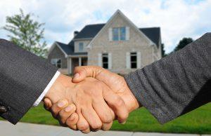uścisk dłoni mężczyzn w garniturach, w tle dom jednorodzinny na przedmieściach