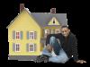 mężczyzna siedzący przed miniaturowym domem